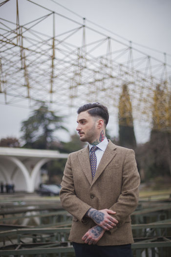 Thoughtful young male model standing against built structure