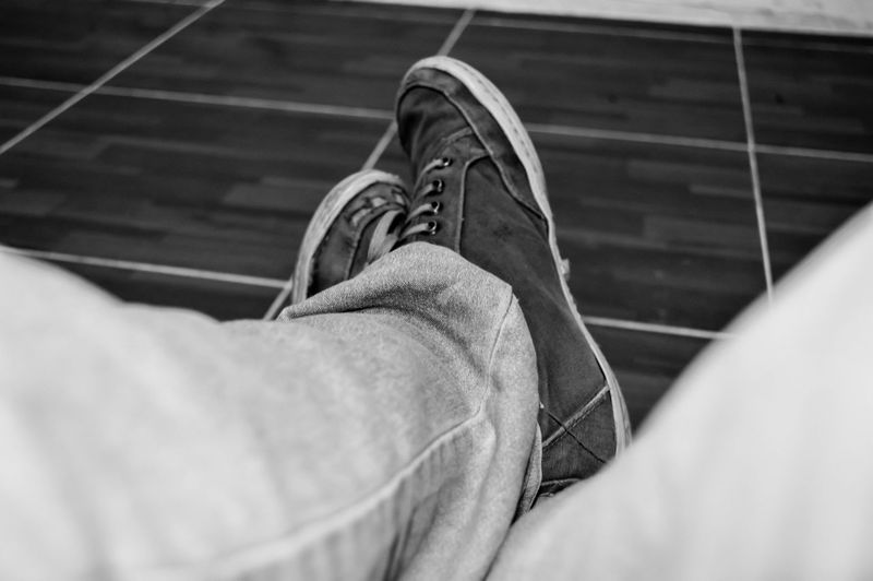 Low Section Of Man Wearing Shoes On Tiled Floor