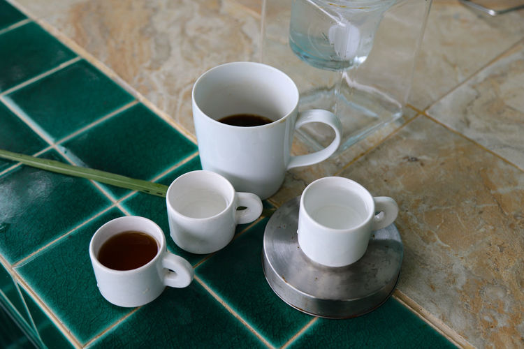 High angle view of coffee and cups on table