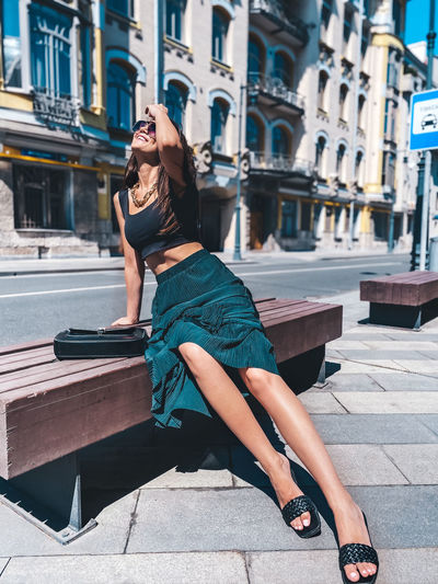 Woman sitting on bench in city