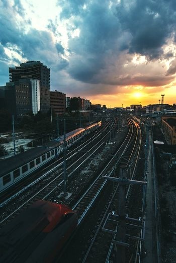 Railway tracks in city against sky during sunset