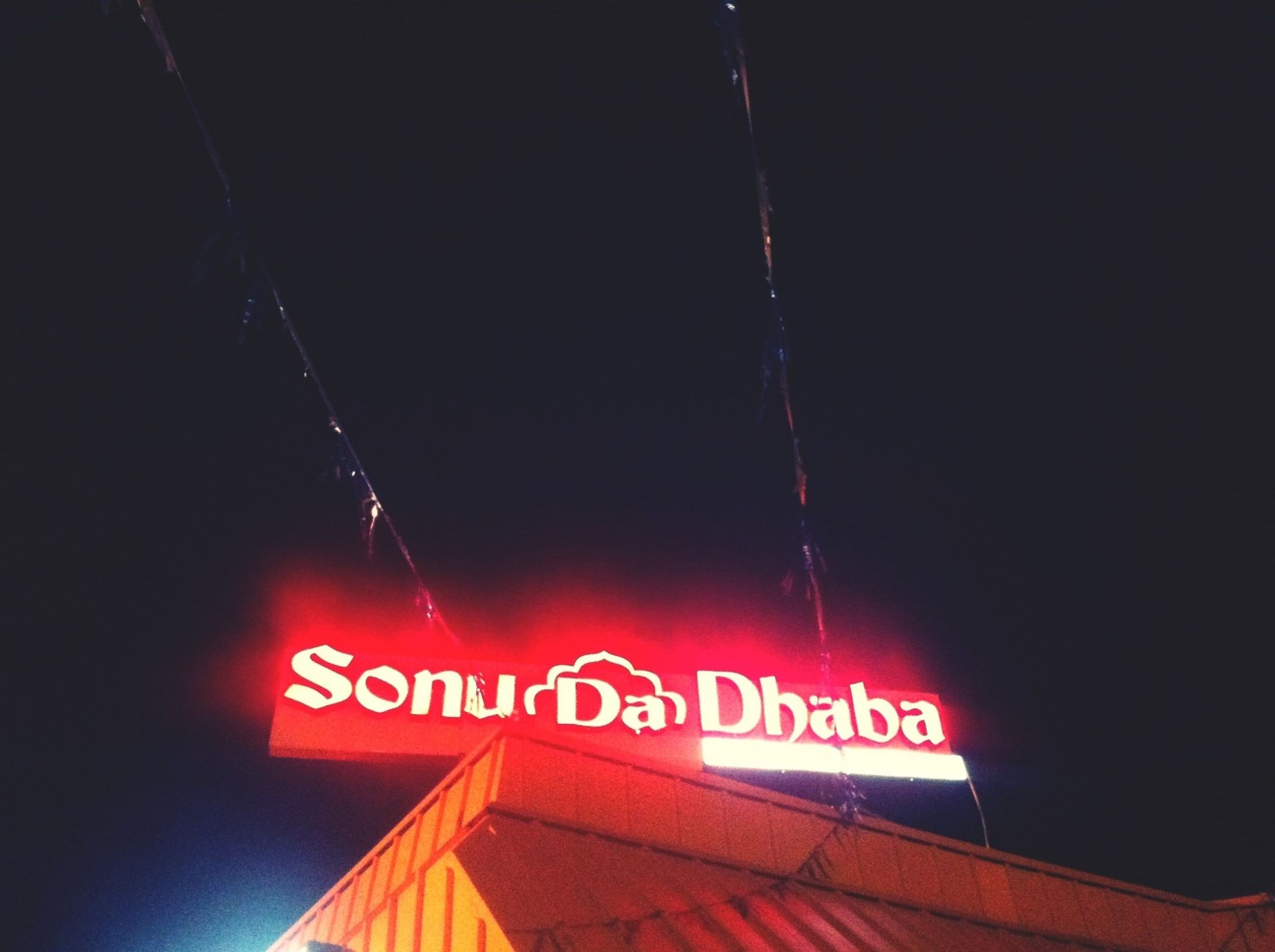 text, communication, western script, low angle view, sign, night, capital letter, information, non-western script, illuminated, guidance, red, information sign, no people, built structure, outdoors, lighting equipment, clear sky, copy space, architecture