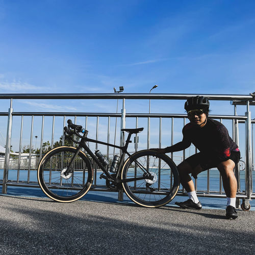 Man riding bicycle on railing against blue sky