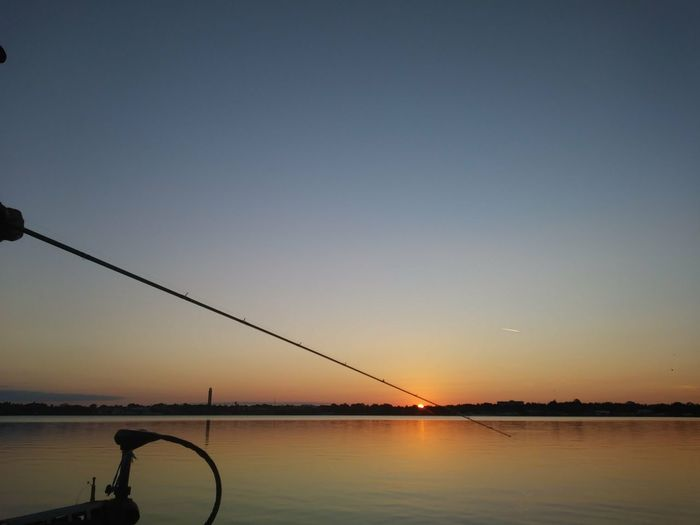 Silhouette fishing rod by sea against clear sky during sunset