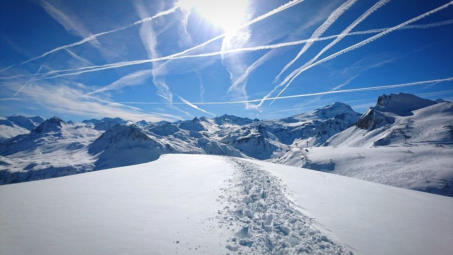 Vapor Trails In Sky Over Snow Covered Mountains