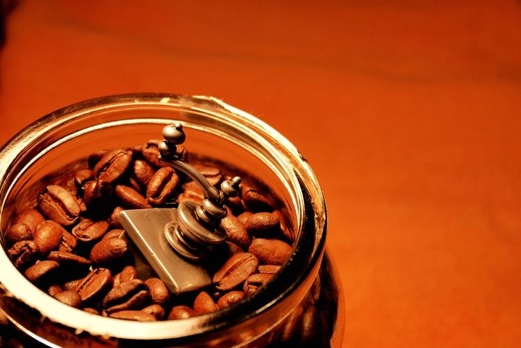High Angle View Of Coffee Beans And Grinder In Container