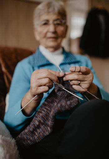 Knitting Needle Knitting Art And Craft Indoors  Wool Textile Craft Sitting Senior Adult Adult Skill  Creativity Eyeglasses  Focus On Foreground Thread One Person Concentration Glasses Holding Front View Sewing Needle Stricken Granny Knitting Knit