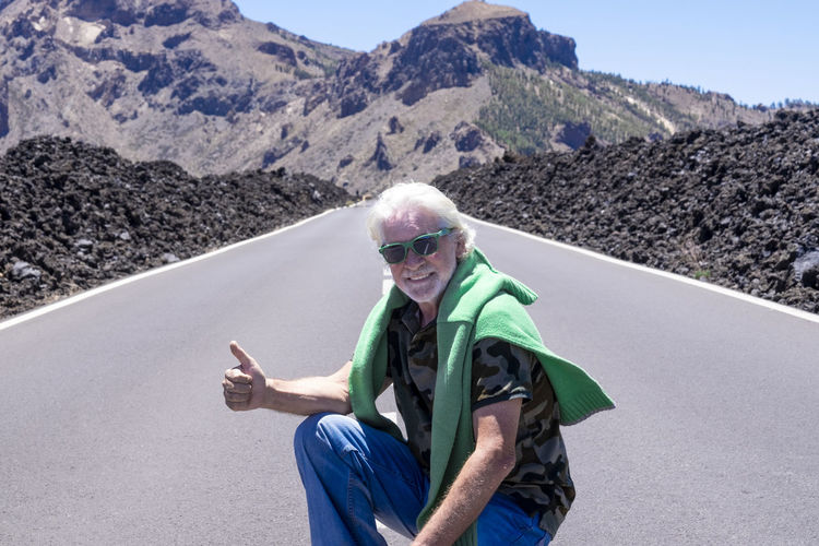 Portrait of smiling man gesturing while crouching on road