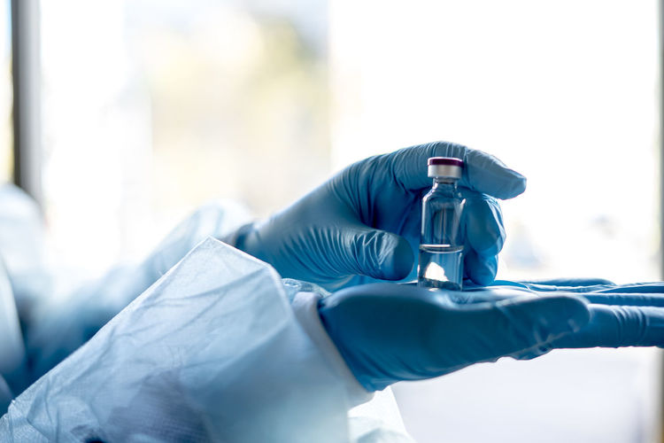 Close-up of scientists hands holding vial