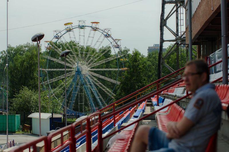 Man in amusement park against sky