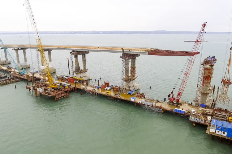bridge, construction, road, railway, kerch, crimea, strait, sanctions, connect, arch, navigable, sea, azov, black, crane, piles, concrete, engineering, helicopter, sky, platform, industrial, industry, building, machinery, steel, equipment, heavy, transportation, facility, plant, under, development, incident, site, oilrig, megastructure, installation, yellow, facilities, production, russia, offshore, column, design, source, occupation, view, beam, high Bridge, Construction, Road, Railway, Kerch, Crimea, Strait, Sanctions, Connect, Arch, Navigable, Sea, Azov, Black, Crane, Piles, Concrete, Engineering, Helicopter, Sky, Platform, Industrial, Industry, Building, Machinery, Steel, Equipment, Heavy, Transpor Built Structure Cargo Container Commercial Dock Crane - Construction Machinery Day Drilling Rig Freight Transportation Industry Nautical Vessel No People Oil Industry Outdoors Sea Shipping  Shipyard Transportation Water Waterfront