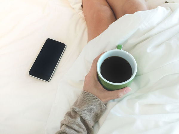 At Home Bed Coffee - Drink Coffee Cup Colors Comfort Cozy Place Enjoying Life Food And Drink Holiday Human Body Part Human Hand Lifestyles Mobile Phone One Person Portable Information Device Relaxing Wireless Technology Women