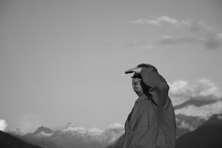 Man shielding eyes while looking away against sky