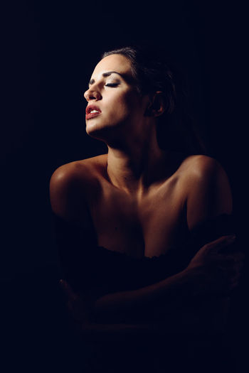 Seductive Topless Woman Against Black Background