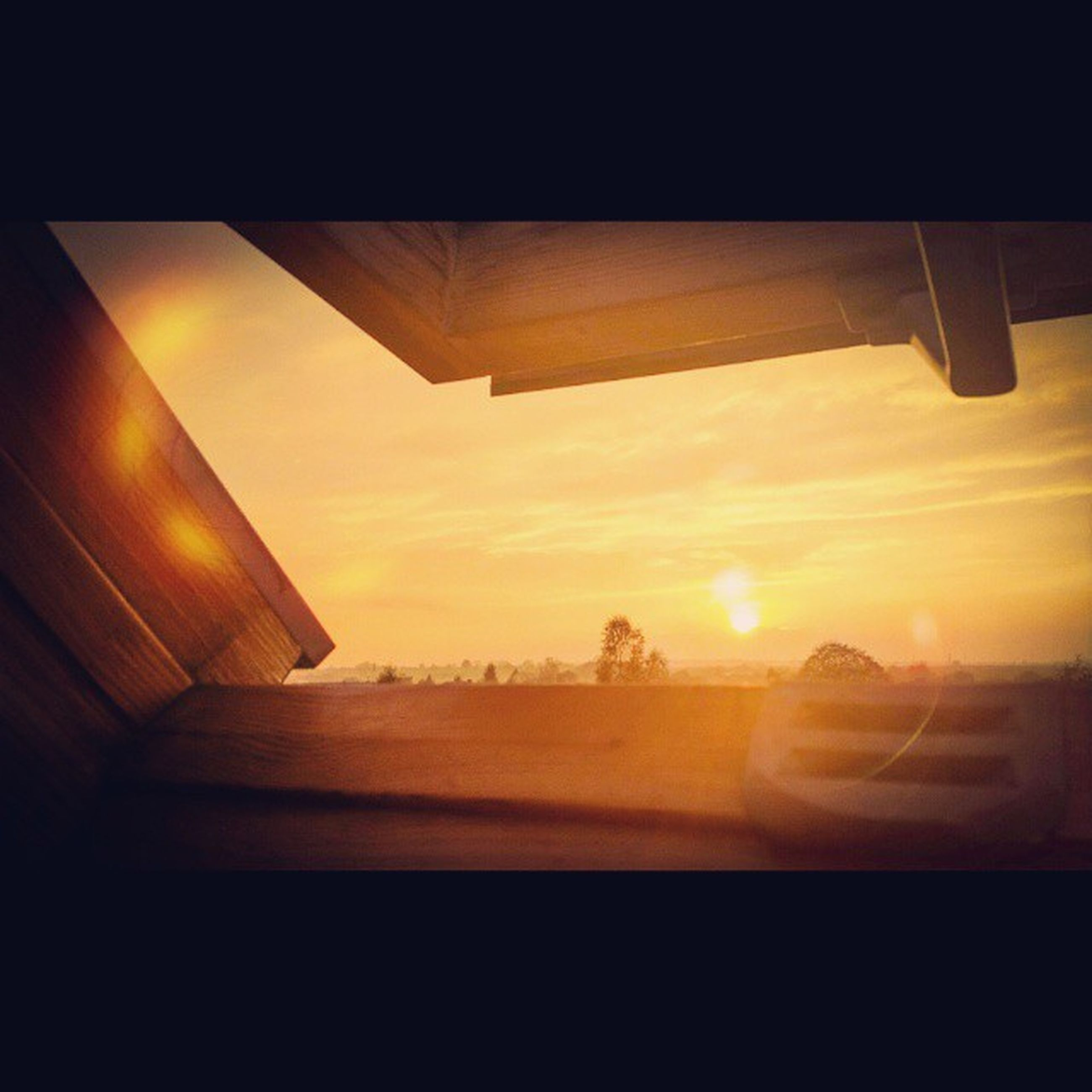 sunset, sun, orange color, transportation, sunlight, sky, built structure, indoors, architecture, glass - material, sunbeam, window, mode of transport, airplane, reflection, lens flare, transparent, no people, air vehicle, silhouette