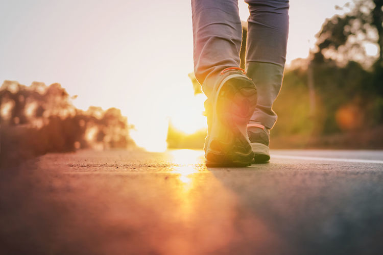 Body Part Bright Human Body Part Human Foot Human Leg Leisure Activity Lens Flare Lifestyles Low Section Nature One Person Outdoors Real People Road Selective Focus Shoe Sky Sport Sunlight Sunset Surface Level Walking