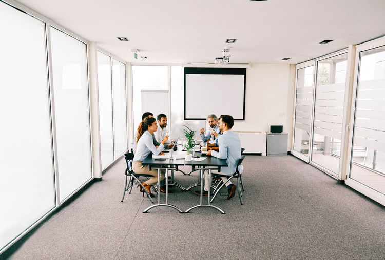 Business people discussing while sitting in board room