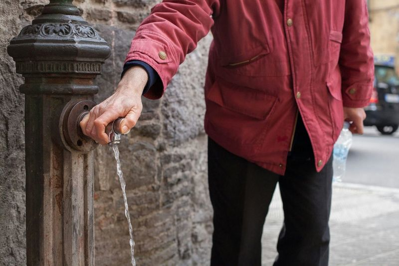 Mid section view of man at water fountain