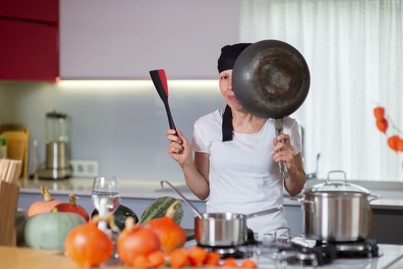 Attractive woman housewife in the home kitchen Autumn Dinner Halloween Holidays Housewife Pumpkins Thanks God Thanksgiving Woman Adult Attractive Domestic Kitchen Fall Food Food And Drink Home Housewife Life Indoors  Kitchen kitchen utensils Lifestyles One Person Pumpkin Season  Thanksgiving Dinner