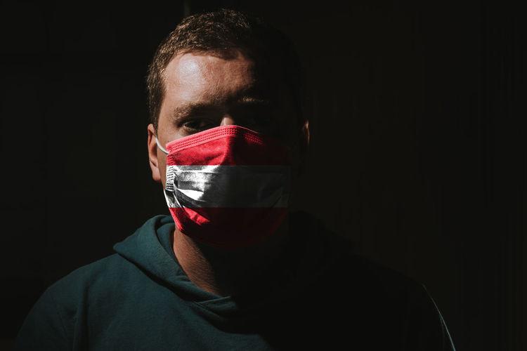 Close-up portrait of man against black background