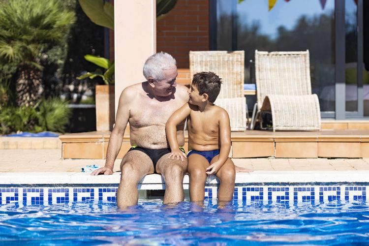 Full length of shirtless man sitting in swimming pool