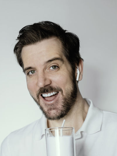 Man with a big smile drinking white milk while wearing white polo shirt and white earbud headphones.