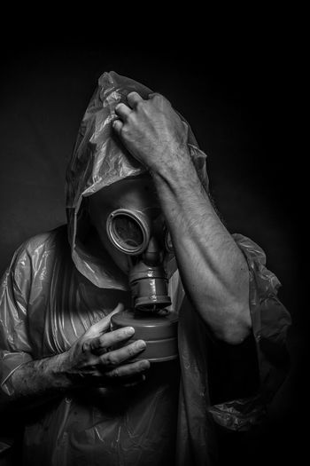 Close-up of man wearing gas mask in darkroom