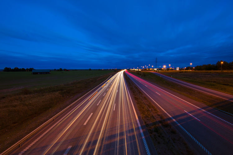 Blue Blurred Motion Diminishing Perspective High Angle View Highway Illuminated Landscape Light Trail Long Exposure Motion Night No People Outdoors Road Road Marking Sky Slow Shutter Speed The Way Forward Transportation Vanishing Point