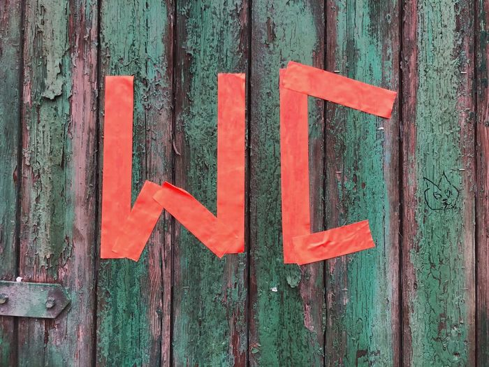 Close-up of red restroom sign on old wooden door