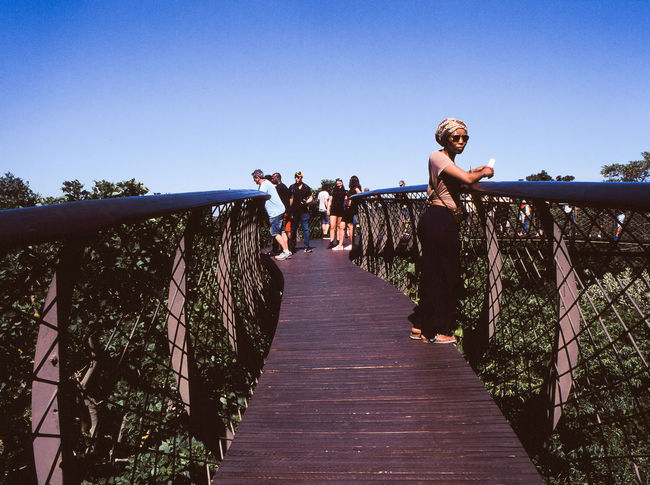 Architecture Bridge Bridge - Man Made Structure Built Structure Clear Sky Day Direction Footbridge Full Length Group Of People Leisure Activity Lifestyles Men Nature Outdoors People Plant Railing Real People Sky The Way Forward Tourism Tree