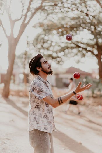 Young man juggling apples on sunny day