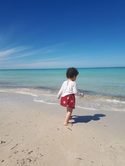 Girl walking at beach against blue sky