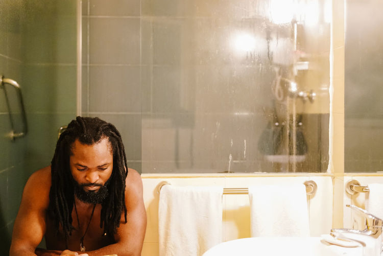 Shirtless man with dreadlocks sitting in bathroom
