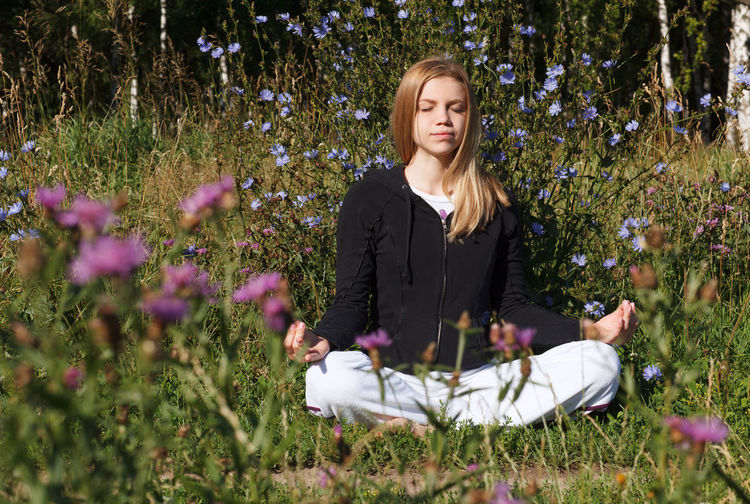 Woman With Eyes Closed Doing Yoga Amidst Flowers On Field