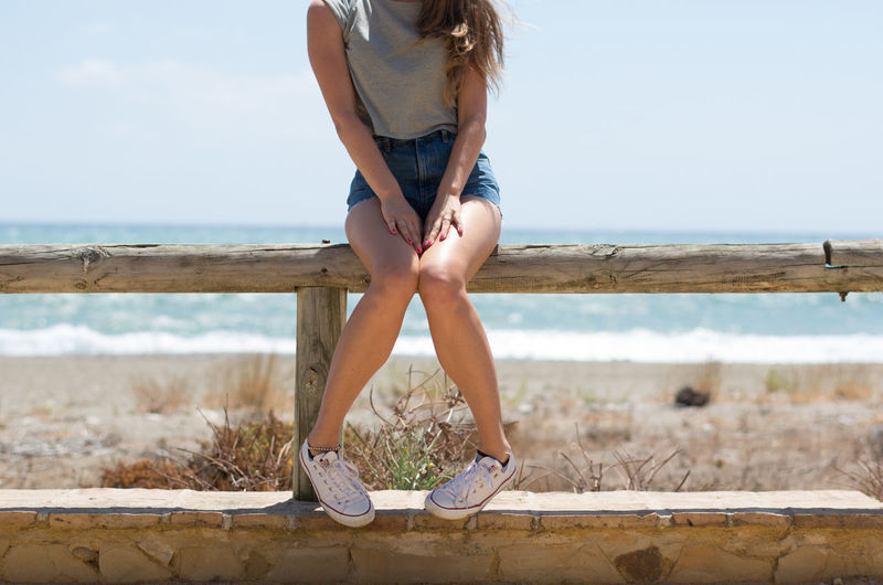 Beach Casual Clothing Converse Day Denim Shorts Girl Horizon Over Water Human Foot Legs No Head Outdoors Person Sea Shore Sitting Sky Tanned Legs Tanned Skin Vacations Water