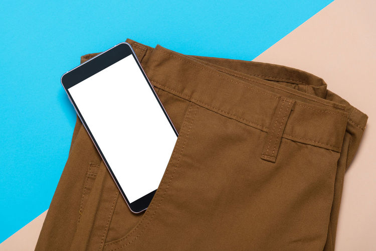 Directly Above View Of Smart Phone In Brown Pant Pocket Against Colored Background