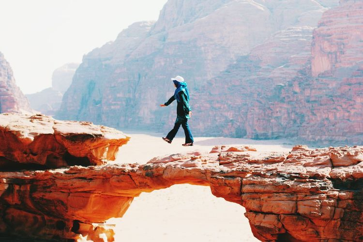 Full length of woman levitating against mountains