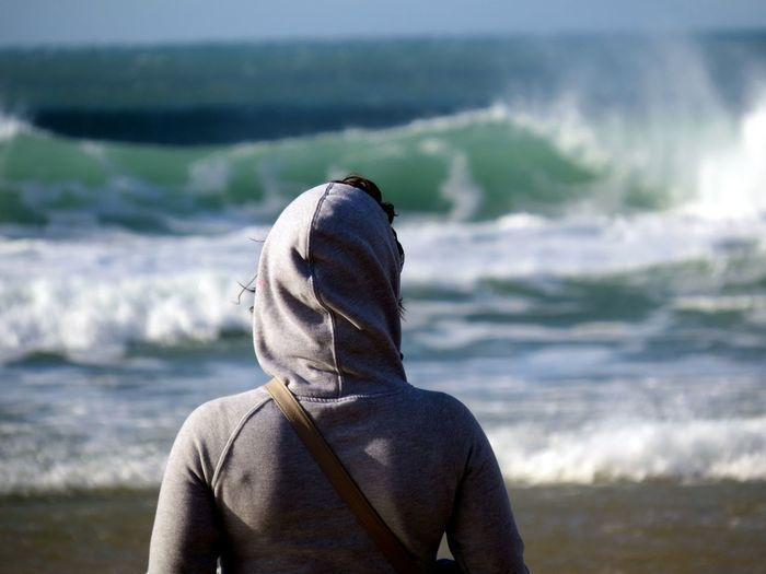Rear view of woman in gray hooded shirt at beach