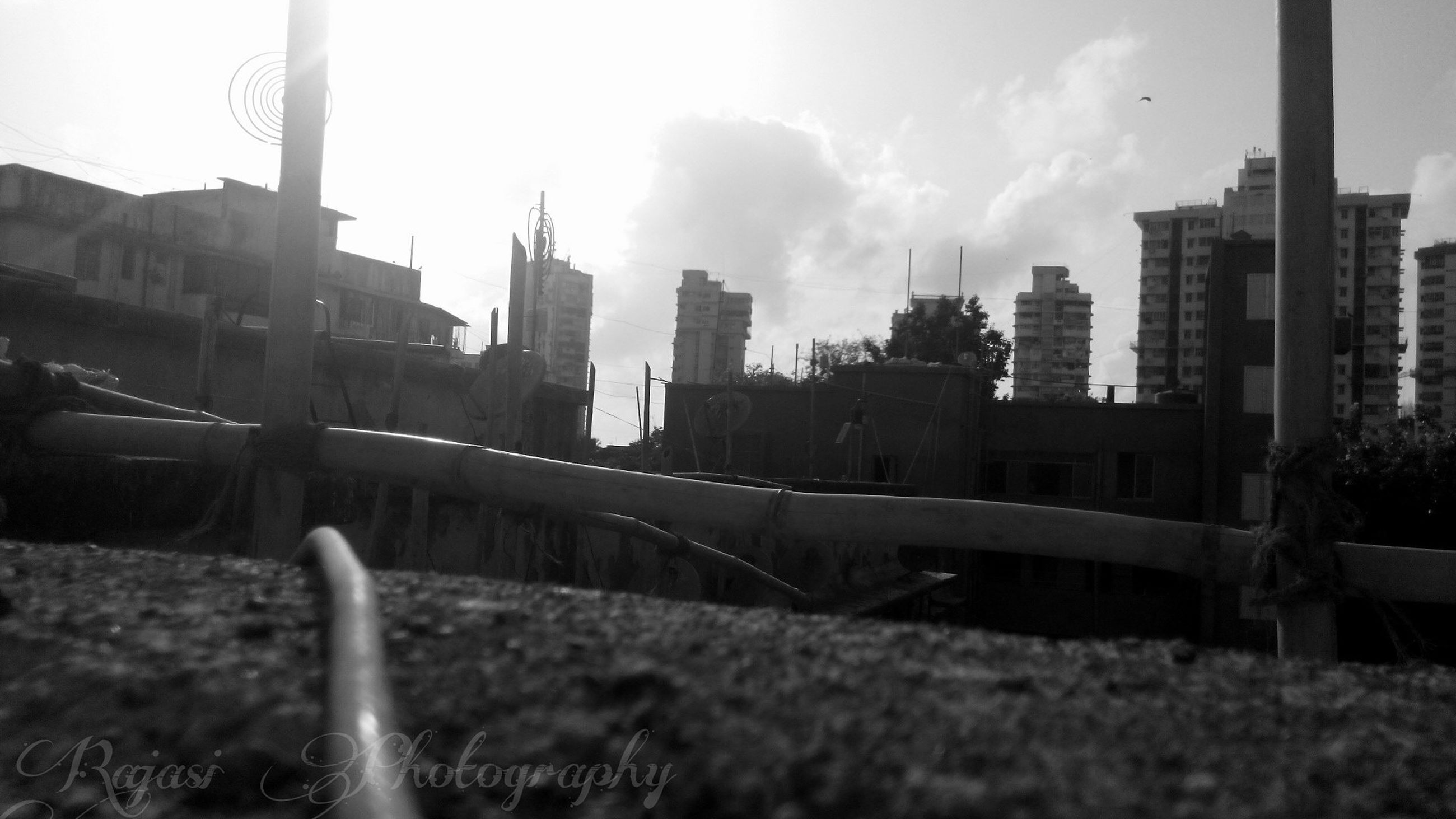 building exterior, architecture, built structure, sky, city, transportation, river, mode of transport, water, nautical vessel, cloud - sky, building, outdoors, no people, grass, cityscape, day, bridge - man made structure, car, sunlight