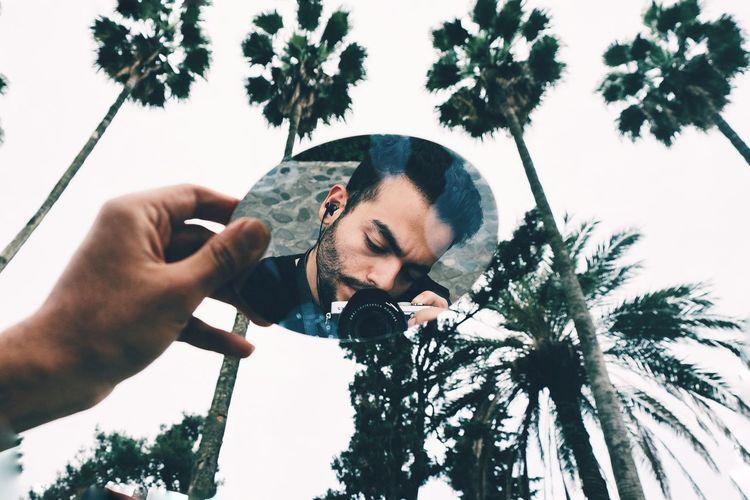 Man Holding Mirror Against Sky