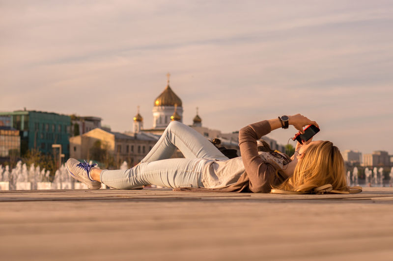 Surface Level View Of Woman Using Mobile Phone While Lying On Walkway Against Temple Of Christ The Savior