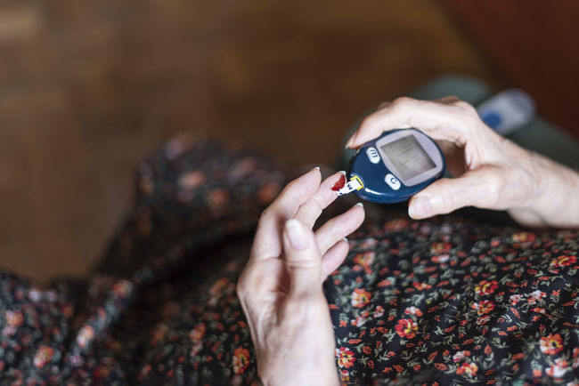 Old lady testing her glucose levels. Health concept. Copy Space Diabetic Sample Analyzing Bloodmoon Chronic  Diabetes Finger Glucose Glucose Meter Hand Health Care Health Concept Holding Hypoglycemia Indoors  Insulin Lancet Meteorology Old_lady One Person Patient Technology Test Tracking