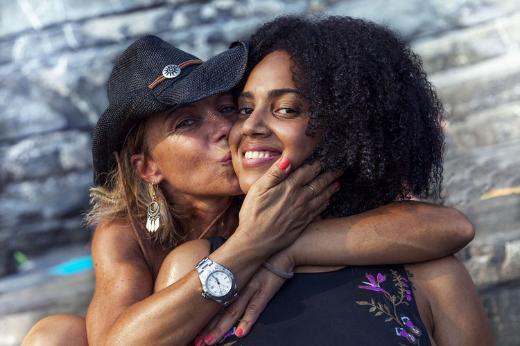 Portrait Of Mother Kissing On Daughter Cheek