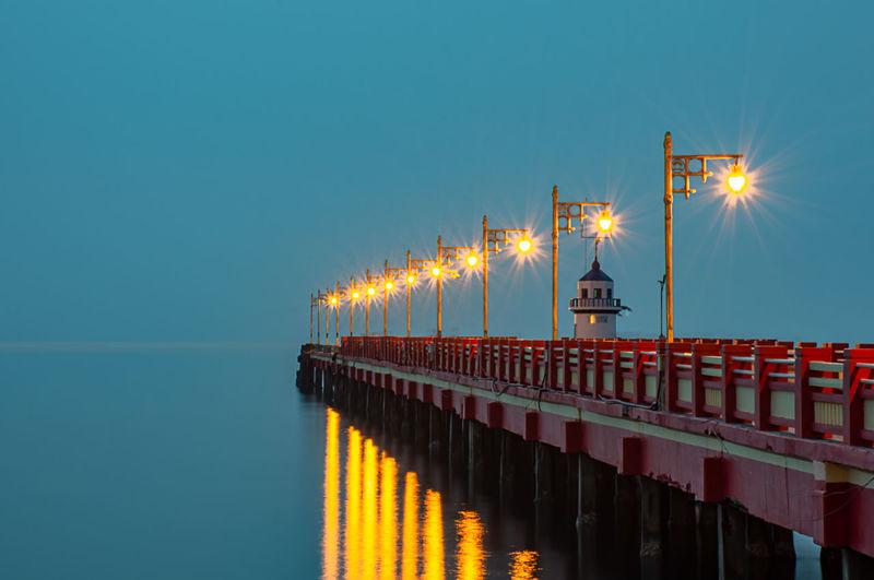 Illuminated street light on bridge over sea against clear sky at night