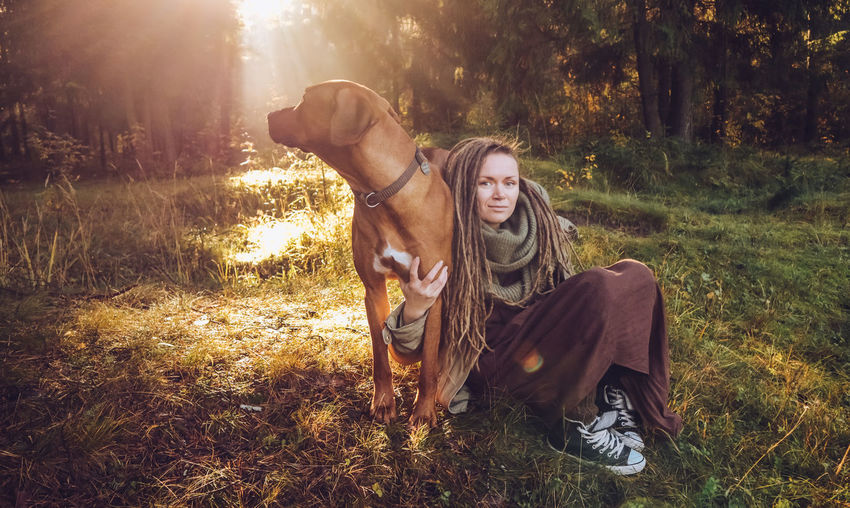 Young smiling woman with dreadlocks in autumn fall forest in the morning sunshine playing with a dog ridgeback Domestic Mammal One Animal Pets Domestic Animals Vertebrate Dog Canine Land Tree Plant Nature One Person Real People Field Sunlight Sitting Outdoors Pet Owner Dreadlocks Ridgeback Autumn Mood 50 Ways Of Seeing: Gratitude