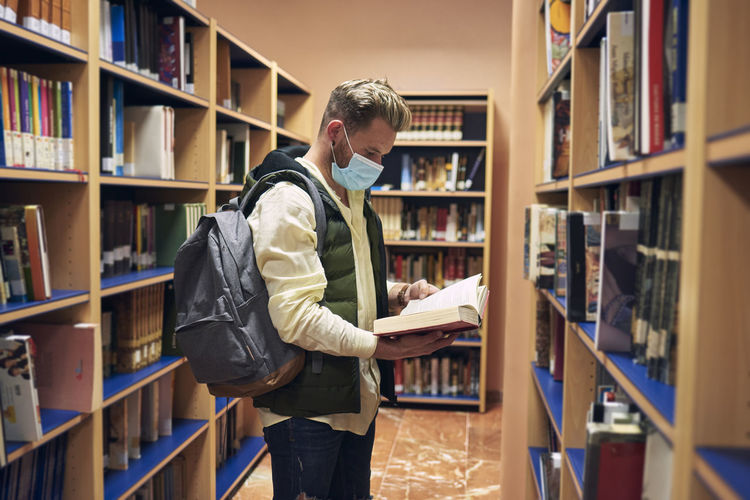 Young man with a mask is reading books in the university library