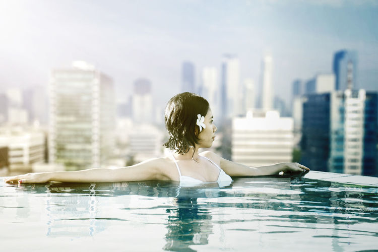 Woman relaxing in swimming pool against cityscape