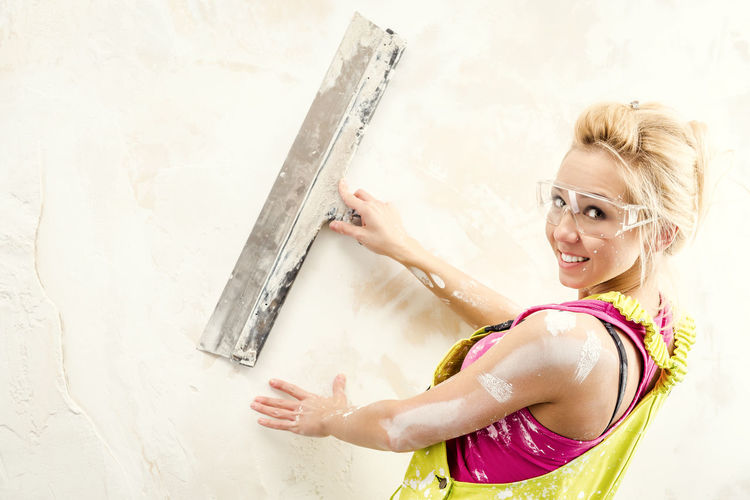 Portrait of young woman in coveralls working with putty knife against white wall