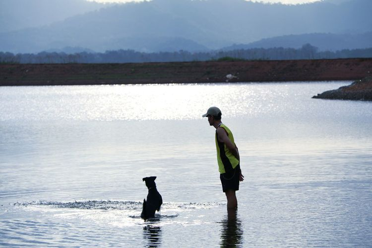 Man with dog in shallow water