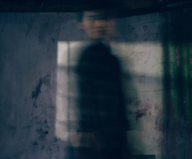 Blurred image of man standing by wall